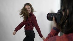 A sessão de foto de um giro modelo novo do estudante fêmea e do sorriso à câmara digital para mulheres cobre o compartimento - filme