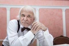 Sessanta anni di uomo dai capelli grigi in una camicia ed in un farfallino bianchi Fotografie Stock Libere da Diritti