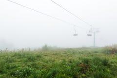 Sesselbahn im Nebel stockfotografie