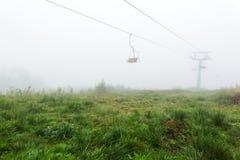 Sesselbahn im Nebel lizenzfreie stockbilder