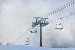 Sessellift in den Wolken im Winter lizenzfreie stockfotografie