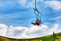 Sessellift, der über Bäume im Sommer auf Berg hinausgeht Stockfotografie
