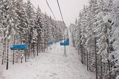 Sessellift im schneebedeckten Wald Stockbilder