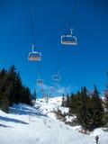 Sessellift mit orange Sitzen auf blauem Himmel Stockfotos