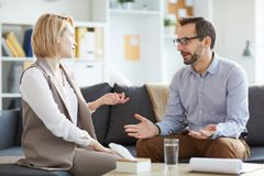 Session on couch. Confident counselor and his patient sitting on couch and discussing problems of young women during session stock images