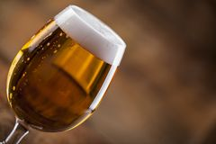 A glass with beer and foam. Session with a glass of beer and a closet in macro close-ups royalty free stock images