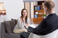 Session with psychotherapist is helpful. Young pretty girl talking excitedly about her life to young elegant psychotherapist at man's cabinet. Man making notes Royalty Free Stock Image