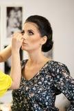 Sessione di trucco con la bella giovane donna castana Truccatore che fa le sopracciglia di una signora attraente dei capelli scur Fotografia Stock