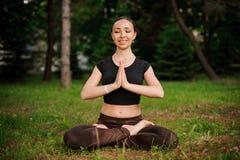 Sessione di yoga della natura in bello legno verde, fra gli alberi Meditazione - namaste nella posa del loto Immagine Stock Libera da Diritti