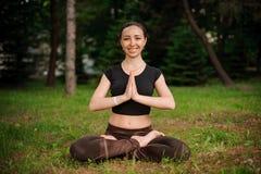 Sessione di yoga della natura in bello legno verde, fra gli alberi Meditazione - namaste nella posa del loto Immagine Stock