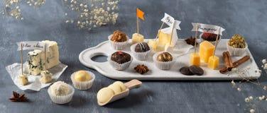 Set świetni czekoladowi cukierki i ser Bielu, ciemnej i dojnej czekolada, brie, błękitny ser, koźli parmisan na talerzu, ser, i obraz stock