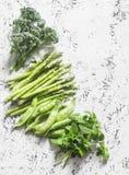 Set świezi organicznie zieleni warzywa - brokuły, zieleni grochy, asparagus, oregano na lekkim tle Karmowy tło, odgórny widok Obrazy Stock