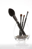 A set of 4 make-up brushes in a transparent glass Stock Image