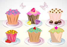 Set of 6 cute cupcakes on the plates Royalty Free Stock Photos