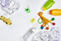 Set of accessories for baby. Pacifier, bottle, diaper, cream on white background. Maternal concept top view stock image