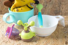 Set of accessories for the baby - pacifier, spoon and bowl. On wood table Stock Photos