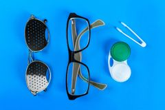 A set of accessories for sight. Medical concept. Pinhole glasses, lenses with container and glasses for sight. Top view Royalty Free Stock Photo