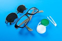 A set of accessories for sight. Pinhole glasses, lenses with container and glasses for sight. Pair of medical pinhole glasses with Stock Photography