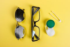 A set of accessories for sight. Pinhole glasses, lenses with container and glasses for sight. Pair of medical pinhole glasses with Stock Image