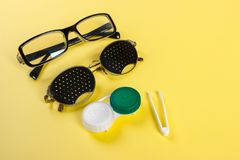 A set of accessories for sight. Pinhole glasses, lenses with container and glasses for sight. Pair of medical pinhole glasses with Royalty Free Stock Images