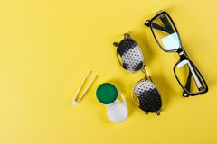 A set of accessories for sight. Pinhole glasses, lenses with container and glasses for sight. Pair of medical pinhole glasses with Stock Photos