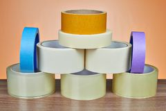 Set of adhesive tape is stacked in form of pyramid. Many rolls of scotch packing tape, and masking tape is stacked in form of pyramid, on orange background Royalty Free Stock Photo