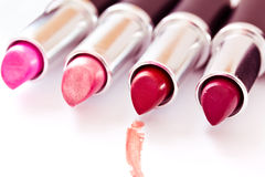 Set of aligned lipsticks with red stroke. Aligned lipsticks with one red stroke Stock Photography