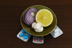 Set of alternative remedies for flu treatment. Including lemon, garlic and onion standing on set of pills on dark wooden table Royalty Free Stock Photo
