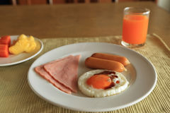 Set of american breakfast on table, fried egg, ham, and sausage with fresh fruits and orange juice Stock Images