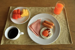 Set of american breakfast on table, fried egg, ham, and sausage, with fresh fruits, orange juice and black coffee. Royalty Free Stock Photos