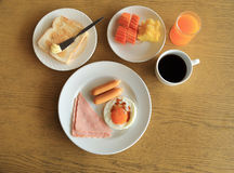 Set of american breakfast on table, fried egg, ham, and sausage, toast and butter, fresh fruits, orange juice and black coffee Stock Images