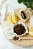 Set for anti-cellulite procedures massage. Coffee scrub, coffee grains, sea salt, lemon, essential oil, soap and sponge on wooden royalty free stock image