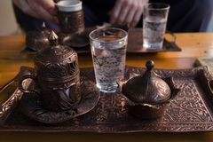 A set of antique Turkish dishes for coffee is on the table. Of a Turkish cafe. Also on the table are glasses of water. In the background, men`s hands hold a cup Royalty Free Stock Photography