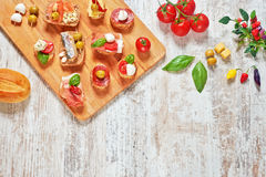 Set of appetizers / snacks / tapas on a wooden table. Mix of appetizers / snacks. Mediterranean tapas or antipasti on a rustic wooden table. Sandwiches with Royalty Free Stock Images