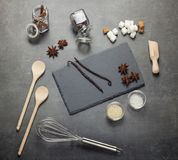 Set of aromatic spices, sesame seeds, salt, sugar and kitchenware, on gray Stock Photos