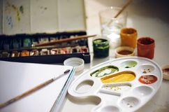 Set of art accessories for drawing: paints, brushes, sketchbook, palette and a Cup of water stock image