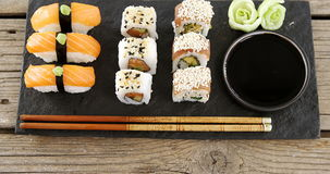 Set of assorted sushi served on black stone slate. Against wooden background stock video footage