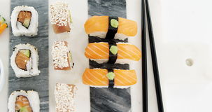 Set of assorted sushi served on gray stone slate. Against white background stock video footage