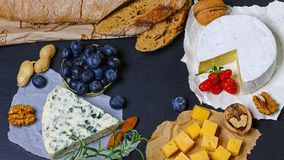 Set of authentic french Cheese - Camembert, Dorblu, Brie. Cheese on a plate with herbs, fruits and nuts. Photo for the menu of res stock photo