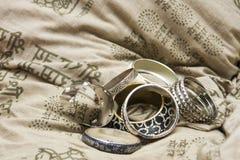 Set av armband på en designkudde arkivbild