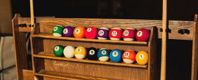 Set of balls for a game of pool billiards on shelves Royalty Free Stock Image