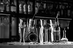 Set of bar accessories for making cocktails, located on the bar, behind is a shelving with liqueurs and strong alcohol. Mixed media royalty free stock images