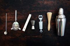 Set of bar or pub accessories. With a martini cocktail shaker arranged in a neat line on a black background stock photography