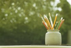 Set barwioni ołówki w ceramicznym szkle na drewnianym stole z zielonym bokeh tłem tylna koncepcji do szkoły Uczeń obraz royalty free