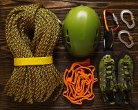 Set of basic climbing equipment on rough wood. Background Stock Image