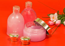 Set for a bath. Two bottles with gel, shampoo, a jar pink colour, white terry towels, a bouquet of colours on a light background royalty free stock images
