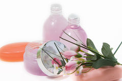 Set for a bath. Two bottles with gel, shampoo, a jar pink colour, white terry towels, a bouquet of colours on a light background royalty free stock photography