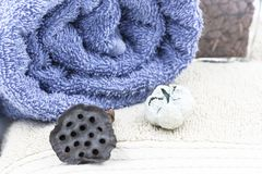 Set of bath towels with dried flowers and blue sea stones stock image