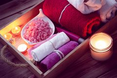 Set of bathhouse accessories for SPA in Low-key lighting. SPA consist from colorful towels, pink sea salt and candles on a wooden tray. Picture in Low-key stock photography