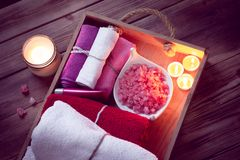 Set of bathhouse accessories for SPA in Low-key lighting. SPA consist from colorful towels, pink sea salt and candles on a wooden tray. Picture in Low-key royalty free stock image
